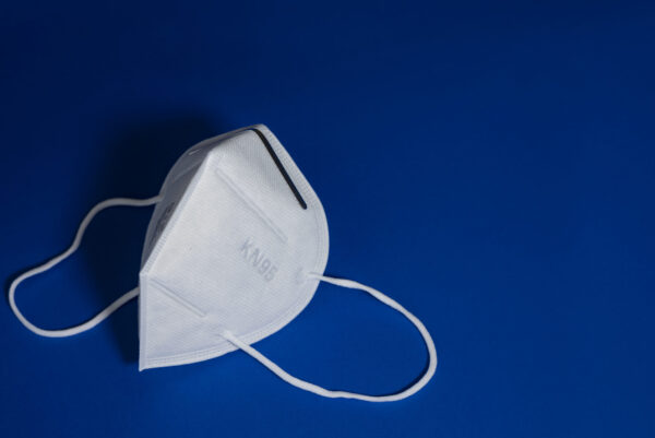 KN95 or N95 white mask with antiviral medical mask for protection against coronavirus on blue background.